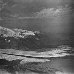 Fourpeaked Glacier, terminus of mountain glacier with dark moraine in the foreground, mountain glaciers in the background (GLACIERS 6518).jpg