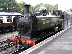 "A green pannier tank locomotive standing at a platform with a red passenger carriage behind. The lettering ""GREAT WESTERN"" is shown in yellow on the side of the pannier tank."