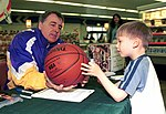 An older man, wearing a purple and yellow jacket is holding a basketball, handed out by a kid who is standing in front of him.