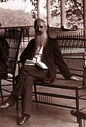 an elderly man with a long beard is seated on a veranda.