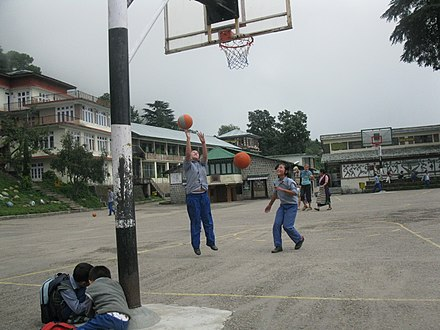 Schoolgirls shooting hoops among the Himalayas in Dharamsala, India. Girls play basketball in Dharmsala, India.jpg