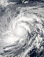 Satellite image of a large tropical cyclone. Though there is no eye, multiple rainbands wrap in an organized fashion about the storm's center.