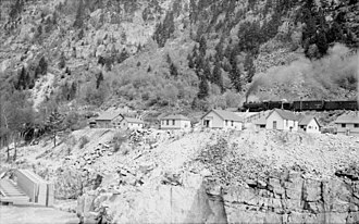 Canadian Pacific Railway in British Columbia - View of Hell's Gate looking across to east bank, w. CPR steam locomotive in background passing old railway housing, c.1945