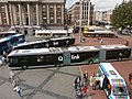 A biarticulated low-floor bus with text written in Dutch on, along with other articulated buses.