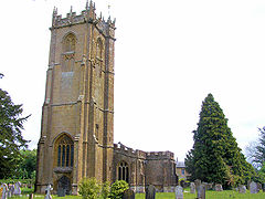 Stone building with arched windows and square tower. In the foreground are gravestones.