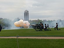 A cannon of the King's Troop Royal Horse Artillery firing in Hyde Park. A large plume of orange smoke, lit orange by the flash from the gun, extends from the barrel.