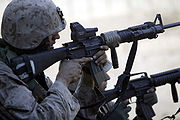 Marine aiming a loaded M16A4 rifle with EOTech optic