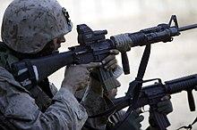 Marsoldato celante ŝarĝitan M16A4-fusilon kun EOTech optika