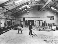 Inside view of the set painting room of the 1907 newly built court theater in Weimar with men who painted theater sets on a large area on the floor with long-handled brushes.  Photo from around 1911.