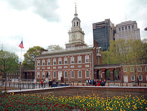 The Front of Independence Hall on an overcast day. The steeple and facade of the building are visible, and an American flagpole stands on the building's right side. The foreground has a flower garden surrounded by a low brick wall with a fence on top. In the background, trees surround the building, and the Penn Mutual Tower and the Penn Mutual Life Building are visible, located to the right of the steeple relative to the viewer.