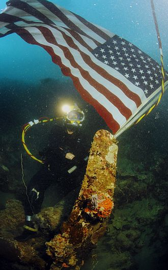 Joint POW/MIA Accounting Command - U.S. Navy divers working with JPAC plant an American flag on the site of a crashed WWII aircraft in the South Pacific