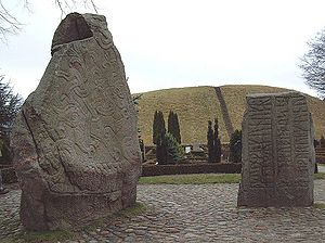 Jelling stones - The heritage site: The runestones in the foreground, in front of the church graveyard. In the far background is one of two mounds.