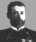 Head of a man with full beard wearing a dark military jacket over a white shirt.