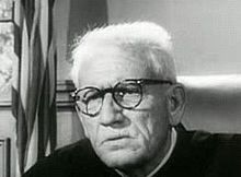 Black and white image of an older man with white hair and wearing glasses looking off to the right.