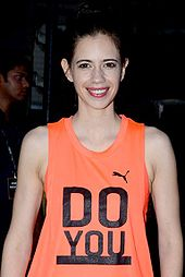 Koechlin smiling at a camera.