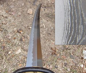 Heat treating - A differentially hardened katana. The bright, wavy line following the hamon, called the nioi, separates the martensitic edge from the pearlitic back. The inset shows a close-up of the nioi, which is made up of individual martensite grains (niye) surrounded by pearlite. The wood-grain appearance comes from layers of different composition.