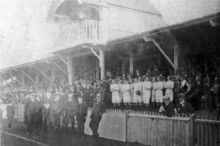 A faded black-and-white photograph of an early 20th-century football stand, crowded with people. An impressive canopy is built into the stand's roof.