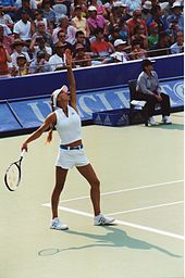 Anna Kournikova playing tennis in white outfit. Left hand is extended as if she has just tossed a ball and right hand is cocking back for the serve.