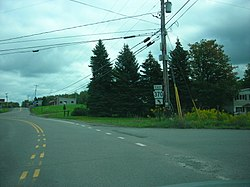 "Image of a paved, marked road, flanked by greenery on both sides. A sign in the center of the photo reads ""EAST 370."""