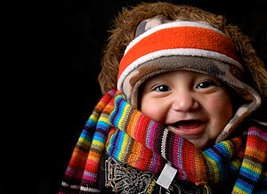 English: A laughing baby under winter clothes ...