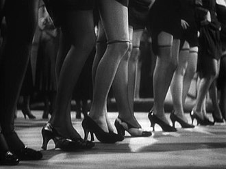 Pre-Code Hollywood - Pre-Code musicals took advantage of their backstage stories to show women in states of dress beyond those considered decent in ordinary life, such as this shot from the trailer for 42nd Street, in which auditioners show their legs to the director.
