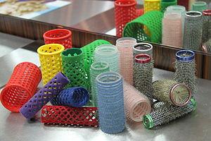 Auf einem schlichten Friseurtisch präsentierte verschiedenfarbige Lockenwickler (kleine Rollen mit feiner Netzstruktur) aus Plastik mit und ohne Häkchen