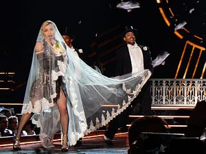 "Material Girl - Madonna, wearing a white bridal veil, performs ""Material Girl"" during the Rebel Heart Tour (2015–16)."