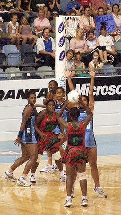 Six players in front of netball basket.  One is the act of shooting, one is trying to block.  Three are in red and three are in blue.