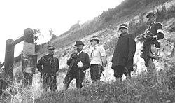 Vijf mannen met snorren - vier militairen en een in burger (met een document onder zijn linkerarm, een vlinderdas en een wandelstok) - staande op de top van een heuvel