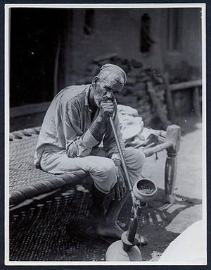 Smoking in India - Man smoking a hookah in India, 1935.