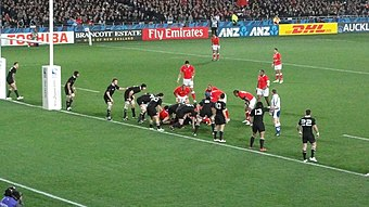 The All Blacks lined up along their try-line, with a ruck formed several metres (yards) from the try-line. Several Tongan players are positions in or around the ruck waiting for the ball to emerge.