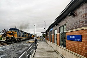 Maywood, Illinois - Maywood Commuter Station with CSX freight train passing.