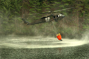 Helicopter bucket - A UH-60 lowers a Bambi bucket into a lake in Michigan.