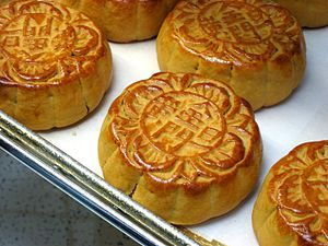 "Mooncake - Mooncakes with Chinese characters 金門蛋黄 (jinmen danhuang), meaning the moon cake contains egg yolk filling and is made from a bakery named ""Golden Gate Bakery"". Mooncakes usually have the bakery name pressed on them."