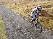 A cross-country mountain biker climbs on an unpaved track