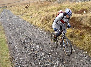 Mountain biking - A cross-country mountain biker climbs on an unpaved track