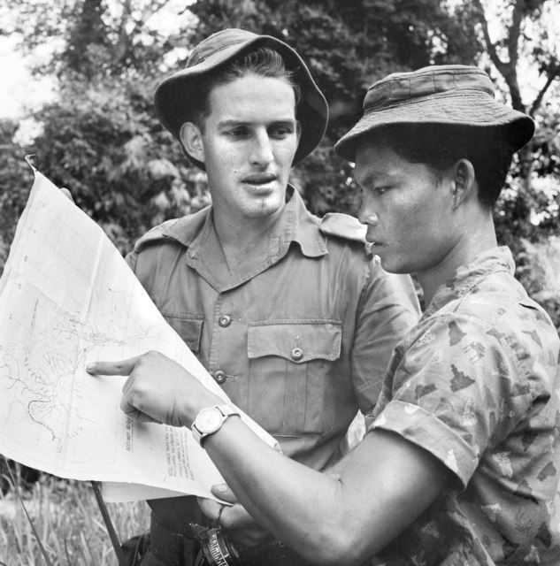 Murut tribesman consulting the map of Sabah with Australian Engineer (AWM CUN-65-0899A-MC)