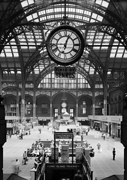 Large high-ceilinged space with round iron arches, covered in glass-dome skylights, floored with vault lights, clock central in foreground.