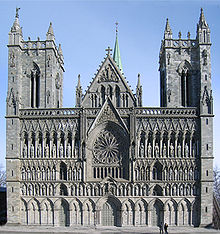 A Romanesque church with Gothic pointed arches. Two rectangular towers separated by a pitched roof entrance hall. The ornate facade is heavily articulated with repeated arches, most of them framing statues.