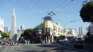 North Beach, San Francisco - Looking southeast from Columbus Avenue (on the left) and Stockton (on the right). The Transamerica Pyramid is visible in the background on Columbus Avenue. The array of overhead wires supply power for the electric trolley buses such as the one seen on Stockton Street.
