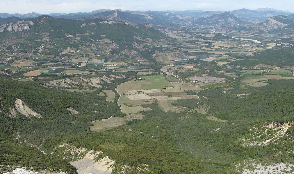 Vue de la commune de Nossage-et-Bénévent depuis la montagne de Chabre. Le territoire communal se termine au niveau du torrent (le Céans) coulant de gauche à droite. A gauche, le haut des falaises d'Orpierre.