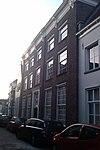foto van Breed woonhuis, ontstaan door samenvoegen van drie vrij smalle huizen achter een brede bakstenen gevel met hardstenen geprofileerde plint en houten kroonlijst van omstreeks 1730
