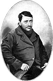 A confident-looking man of about 40 with a large dark beard. The thumb on his left hand is absent.