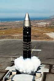 Huge missile with body painted in black rising out of silo during a launch, producing clouds of gas at the silo's opening. In the distant is a coastline.