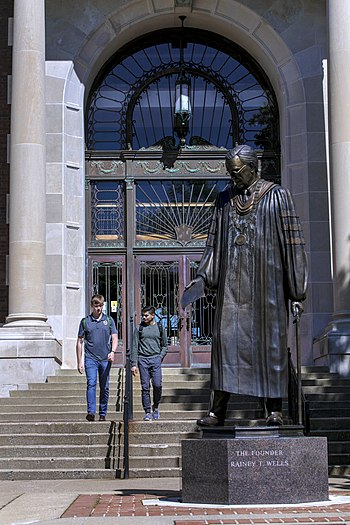 Two students walk out of Pogue Library near the statue of founder Rainey T. Wells.