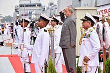 President Mukherjee saluting, surrounded by a naval guard of honour