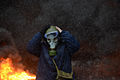 Protester wearing a tear gas mask against background of the massive fire set by protesters to prevent internal forces from crossing the barricade line. Kyiv, Ukraine. Jan 22, 2014.jpg