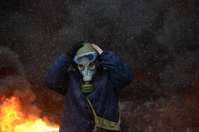 file protester wearing a tear gas mask against background