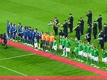 Several men standing on a grass football field. There are twenty five men standing in a straight line; eleven wearing blue on the left, three wearing orange tops and black shorts in the middle, and eleven wearing green on the right. In front of this line is a long narrow piece of red carpet. Behind the line are several middle aged or elderly men, wearing black and playing a variety of brass and percussion musical instruments.