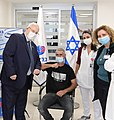 Reuven Rivlin with the first vaccinator in Phase B of the Israeli Vaccine of the Israeli Biological Institute, January 2021 (GPOABG 4084).jpg